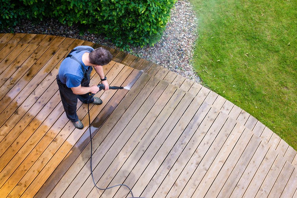 Man Power Washing a Deck