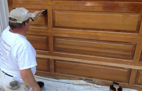 Man Staining Garage Doors
